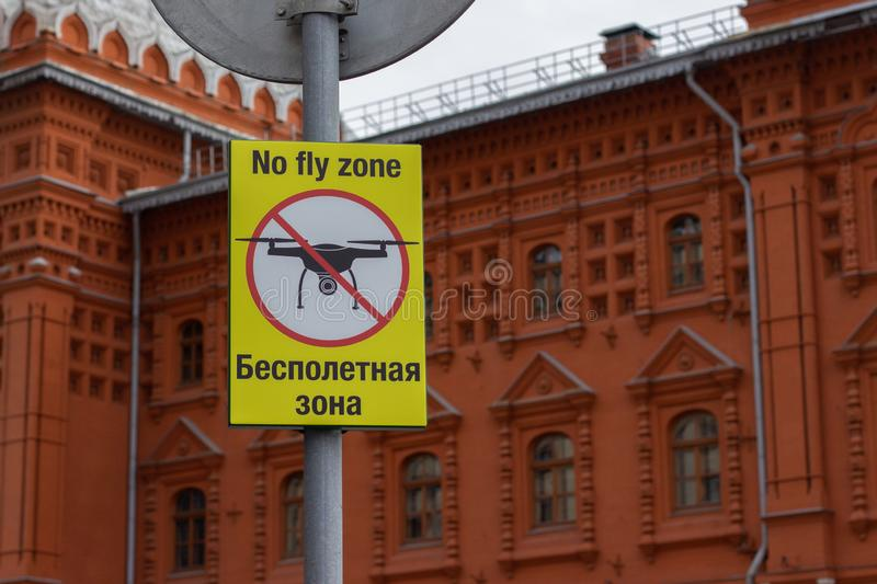 Sign No Fly Zone in English and Russian, the silhouette of the drone crossed out by a prohibition strip. Sign prohibiting flying. Sign No Fly Zone, the royalty free stock images