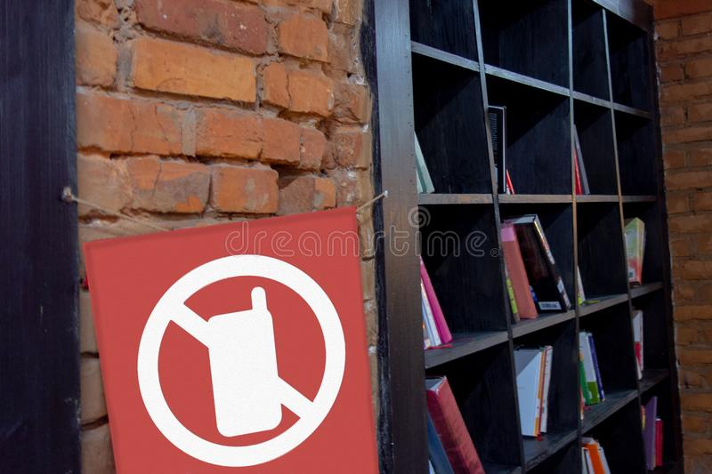 Sign No phone on the library brick wall. Keep silence in public place concept. Paper book against electronic reader or smartphone royalty free stock photos