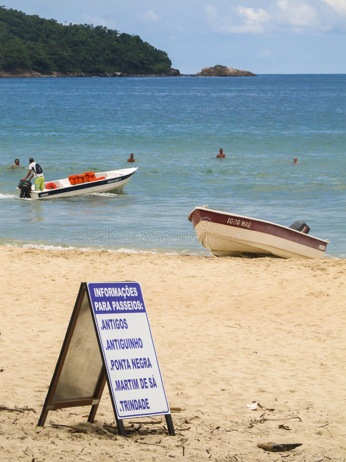 Sign offering boat tours to beaches nearby at Praia do Sono, popular beach in Paraty, Rio de Janeiro. Praia do Sono, Brazil - Circa January, 2013: Sign offering stock image