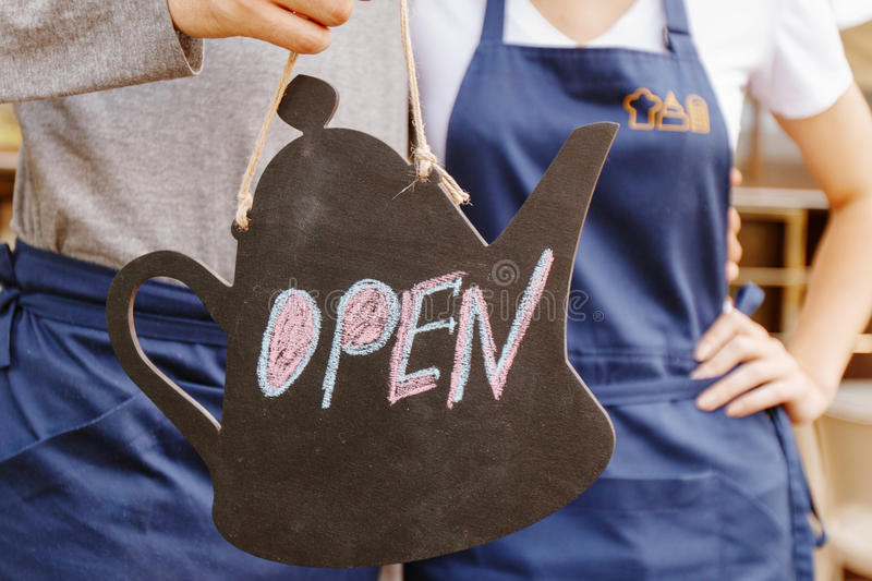 Sign open on background of workers. Always open. Two cafeteria workers holding sign open stock photography