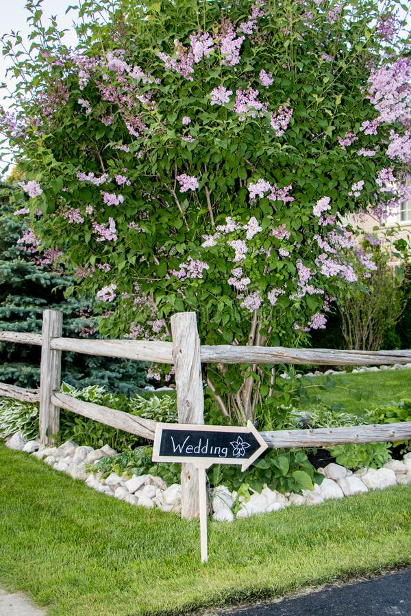 Sign for outdoor summer wedding. Rustic homemade wedding sign for outdoor wedding with lilac tree and wooden fence royalty free stock photos