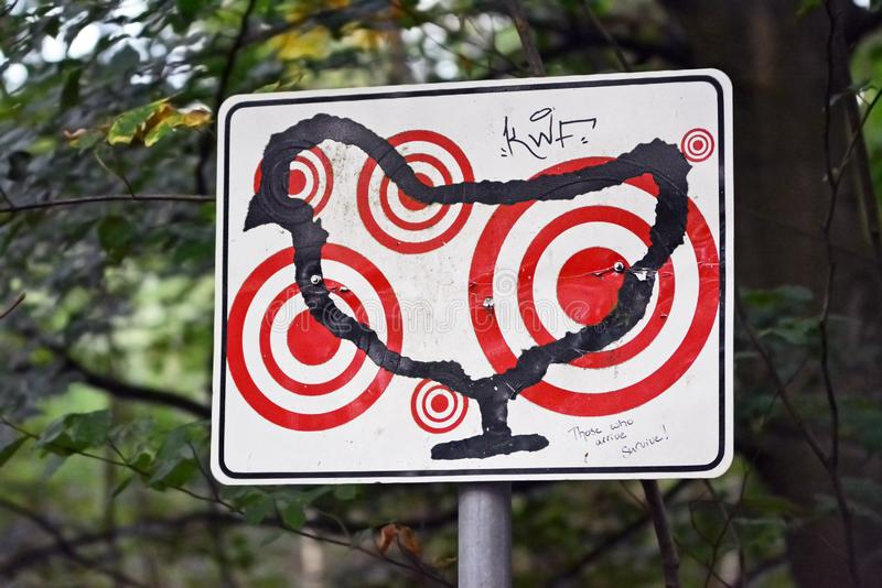 Sign with outlines of a chicken with multiple red target marks on it as part of art exhibition in forest stock photography