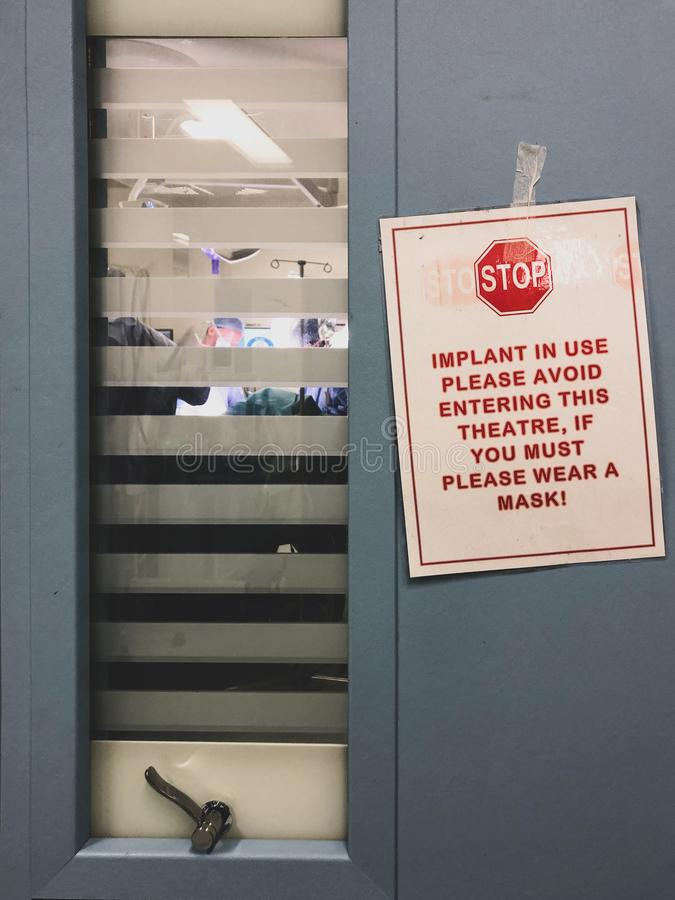 Sign outside operating theatre doors - do not enter - with surgeons visible blurred through window blinds. Such signs are used to reduce infection rates in royalty free stock image