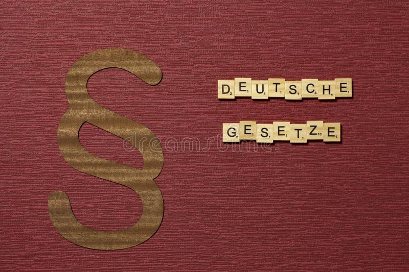 The sign paragraph on the claret color background. Word in german deutsche Gesetze royalty free stock image