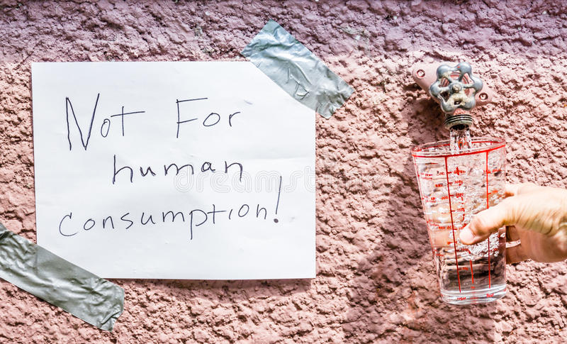 Sign pasted on stone wall saying `not for human consumption`. Horizontal image of a sign saying `not for human consumption` beside an outdoor water tap with a stock photo