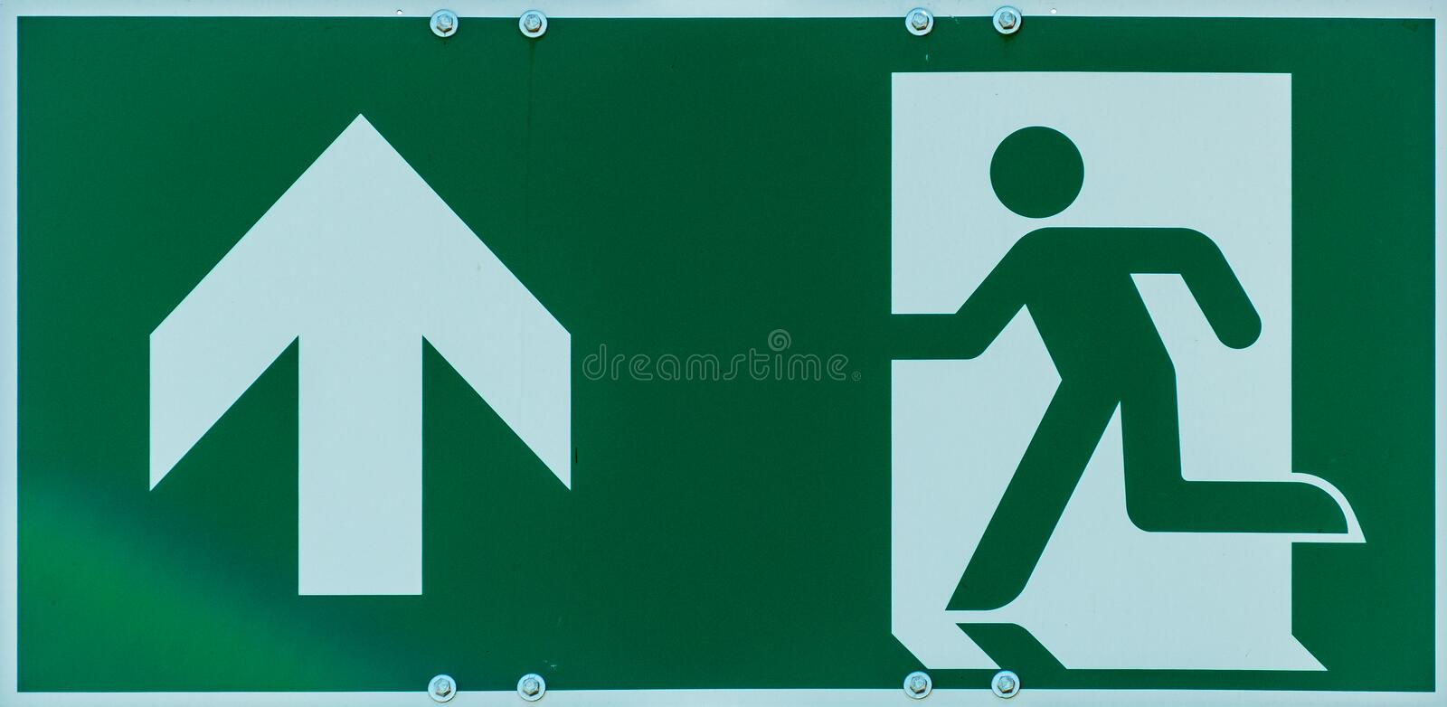 Sign with the pictogram of a walking person and an arrow in white on a green background, indication of an escape route in case of stock photography