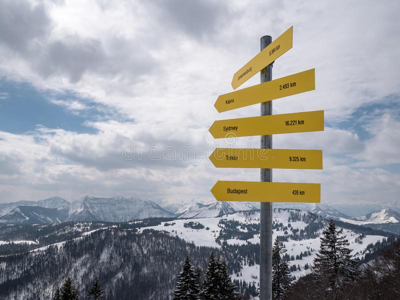 Sign Post in Austrian Alps giving directions to Budapest, Tokyo, Sydney, Cairo and Johannesburg stock photos