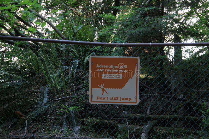 A sign posted on a chain link fence. Warning about cliff jumping there are trees in the background royalty free stock photography
