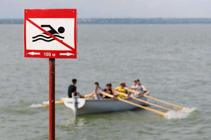 Sign prohibiting swimming in this place on the background of a wooden rowing boat with people.  royalty free stock photos