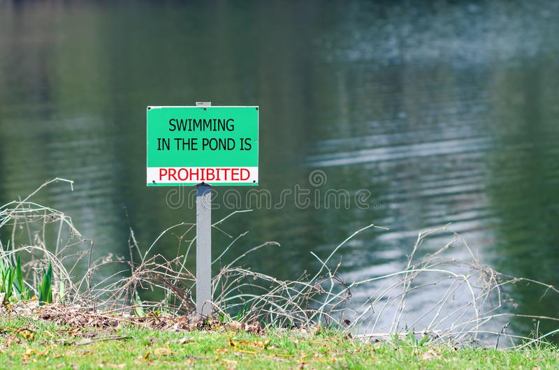 A sign prohibiting swimming in the pond.  royalty free stock images