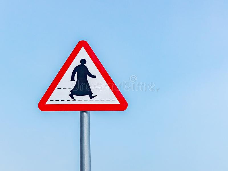 Sign prohibiting traffic for pedestrians in a southern Arab country, a silhouette of a pedestrian in traditional clothes. Against a blue sky stock image
