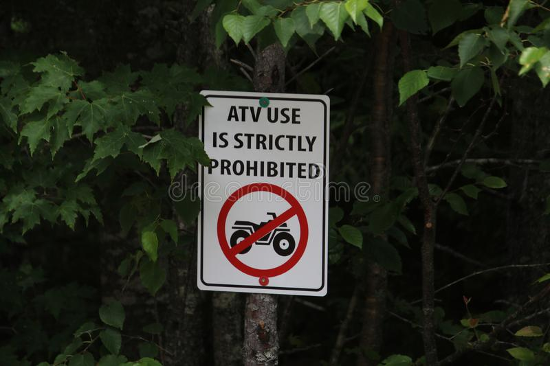 A sign prohibiting the use of ATV& x27;s. In the woods, beware, forbidden, forest, green, information, nature, no, outdoor, park, prohibited, red, symbol royalty free stock images
