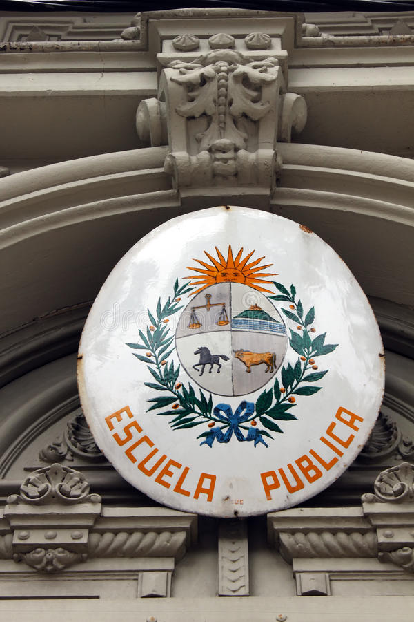 A sign on a public school with Uruguayan coat of arms stock image