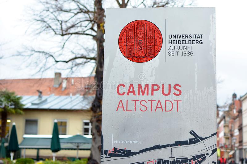 Sign with red university emblem and words `University Heidelberg, future since 1386` and `Campus historic city center`  on stock photo