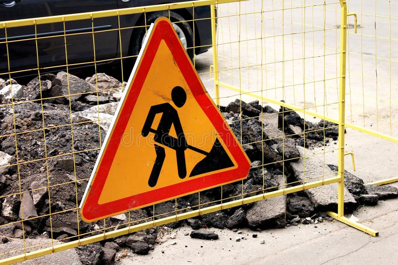 Sign road construction, road maintenance in the city street. Sign road construction, road maintenance on a yellow grid fence and a pile of milled asphalt in the stock images