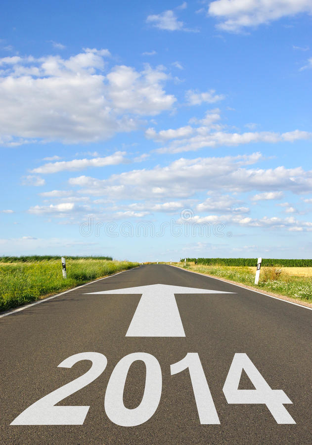 2014 sign on road. 2014 sign on countryside road with arrow receding into distance, summer scene royalty free stock photography