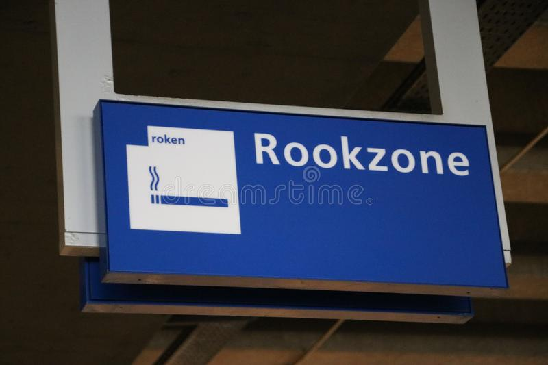 Sign Rookzone in dutch on the Den Haag Centraal railway station to indicate the zone where smoking is allowed royalty free stock photos