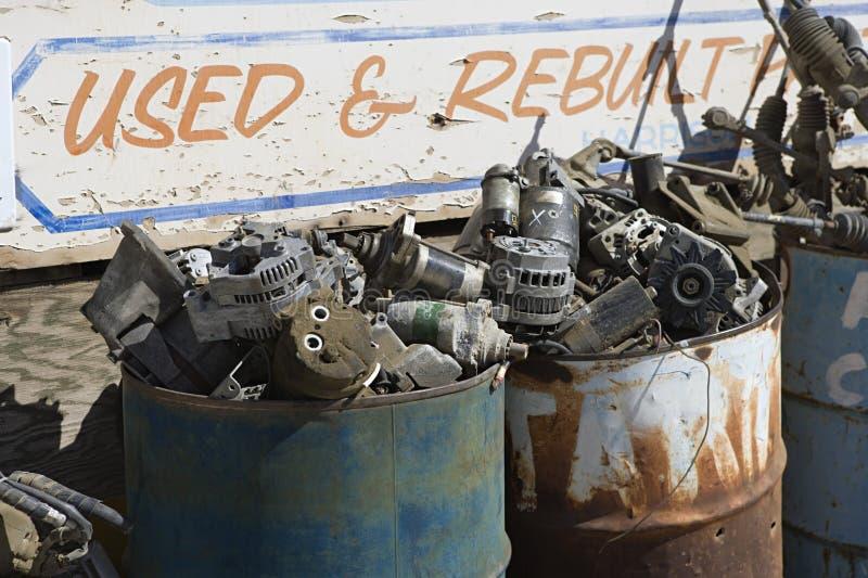 Sign And Rusty Barrels In Junkyard. Torn�down and broken�up car parts in barrels at junkyard royalty free stock photos