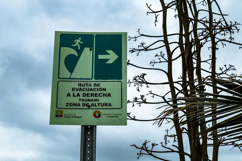 Emergency exit and evacuation signs on a pacific shore of Ecuador. royalty free stock image