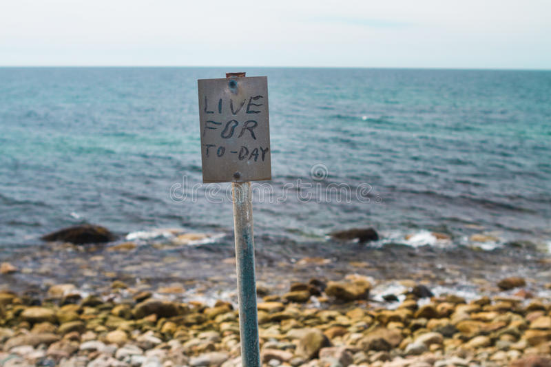 Sign on the shore. The phrase Live for Today is printed on the inspirational signpost on the shore with ocean background stock photos