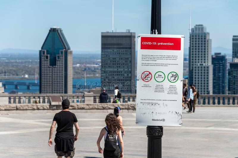 Sign showing Covid-19 safety guidelines in Montreal. Montreal, CA - 18 May 2020 : Sign showing french Covid-19 safety guidelines and Montreal skyline in the royalty free stock image