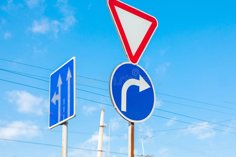 A sign that shows the road and turn only right to the background of a brilliant blue sky.  royalty free stock image