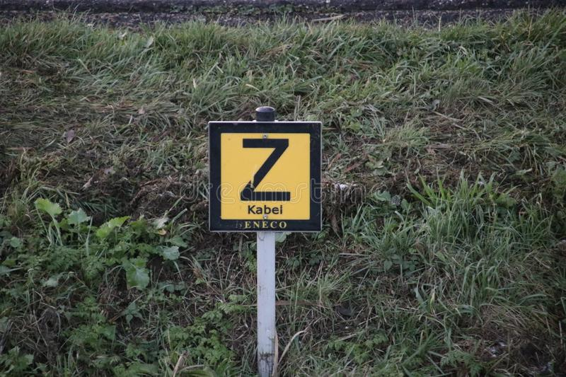 Sign in the side of a ditch to warn that there is an electricity cable sunken in the water. stock photos