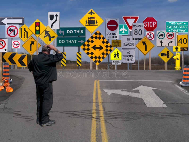 Sign Signs everywhere a sign. Man standing on roadway in front of a birage of signs. Confused of what to do, where to go, being told what to do stock photos