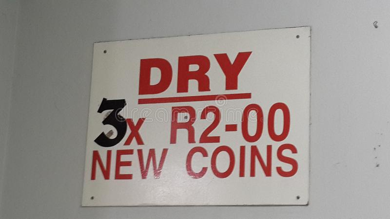 Sign in South Africa with currency, three two rand coins to use dryer. Sign in South Africa with currency, three new two rand coins to use dryer royalty free stock photos