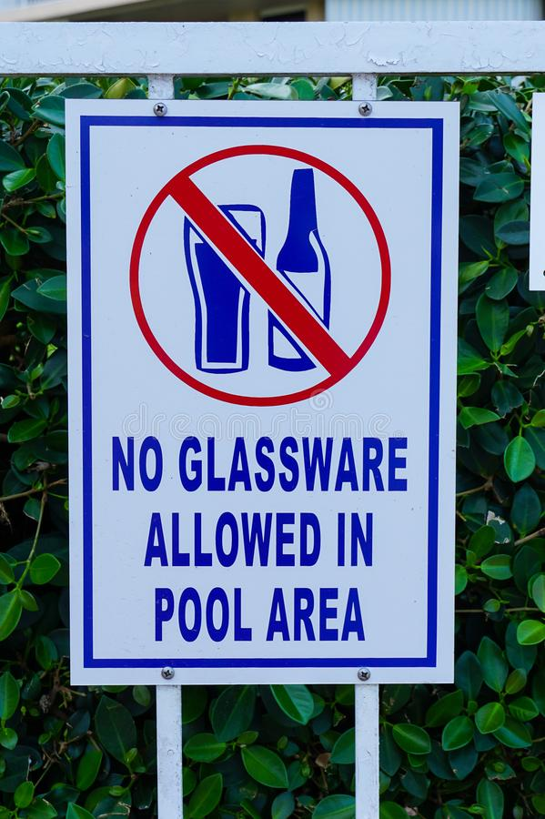 Sign that tells people that glassware is not allowed in the swimming pool area stock photography