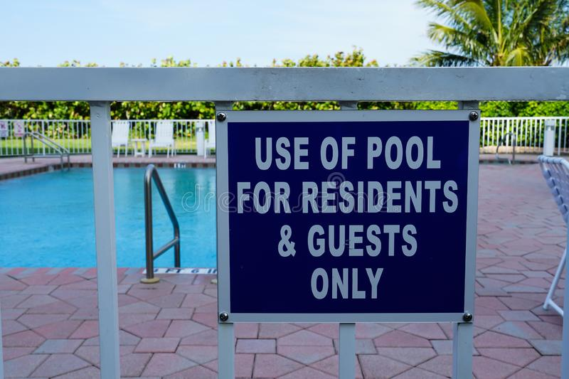 Sign that tells people the pool is for residents and guests only. An outdoor Sign that tells people the pool is for residents and guests only on the gate in stock photo