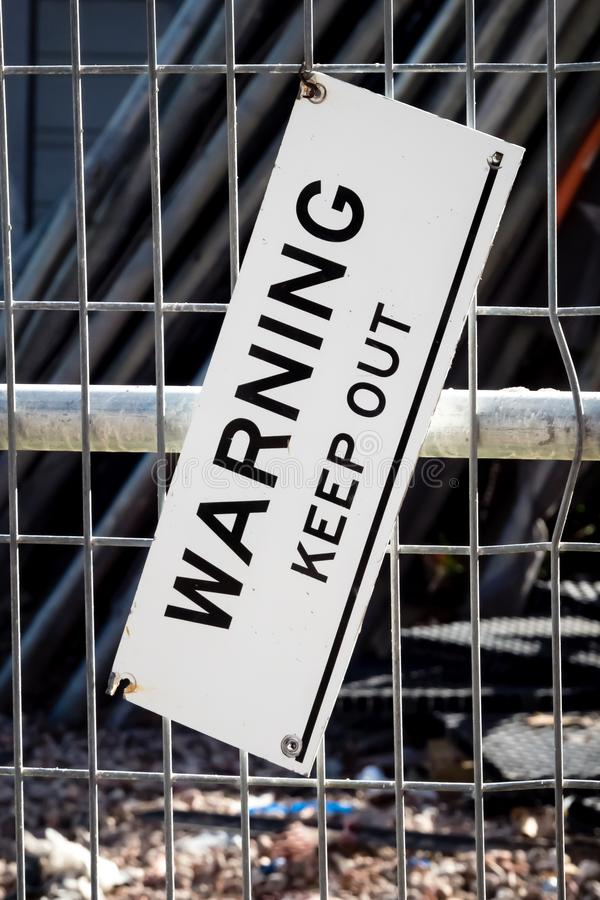 Sign with text WARNING KEEP OUT on fenced building site royalty free stock image