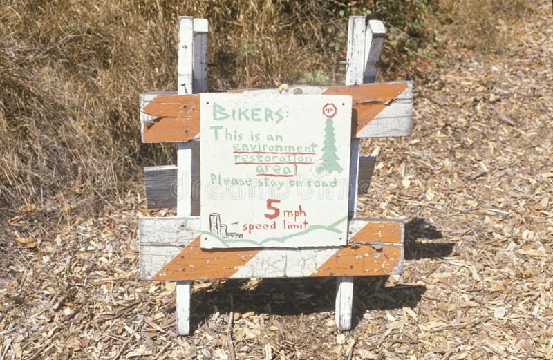 A sign warning bikers of an environmentally sensitive area is present stock photography
