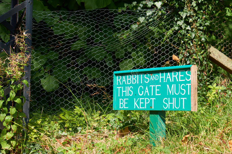 A sign warning of the problem of Rabbits and Hares. Outside a heritage flower garden royalty free stock image