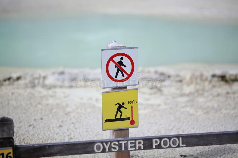 Sign warning on walkway. Red and yellow warning sign with thermal pool stock photography