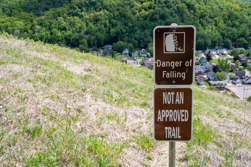 Sign warns hikers of a danger of falling, not an approved trail, to stay out of area. Concept for selfie deaths.  stock images