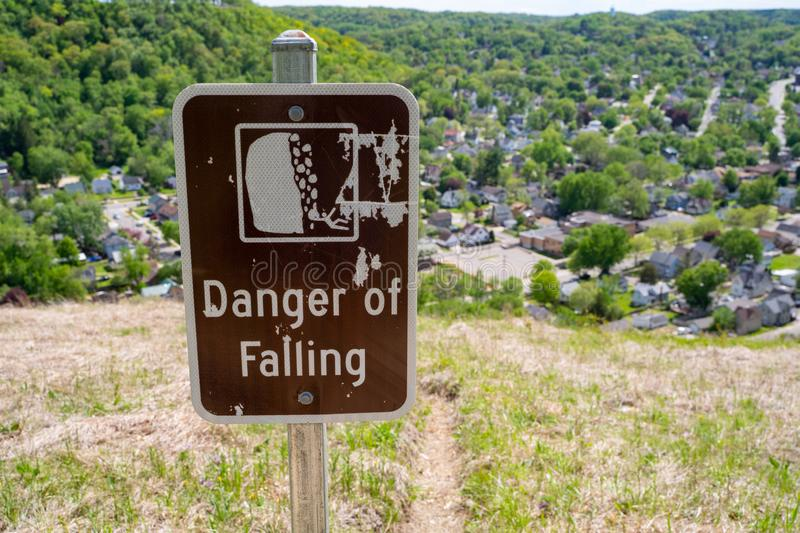 Sign warns hikers of a danger of falling, not an approved trail, to stay out of area. Concept for selfie deaths.  royalty free stock image