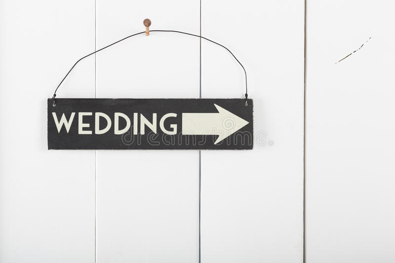 Sign wedding. Wedding sign hanging on a wooden wall pointing the direction wedding royalty free stock images