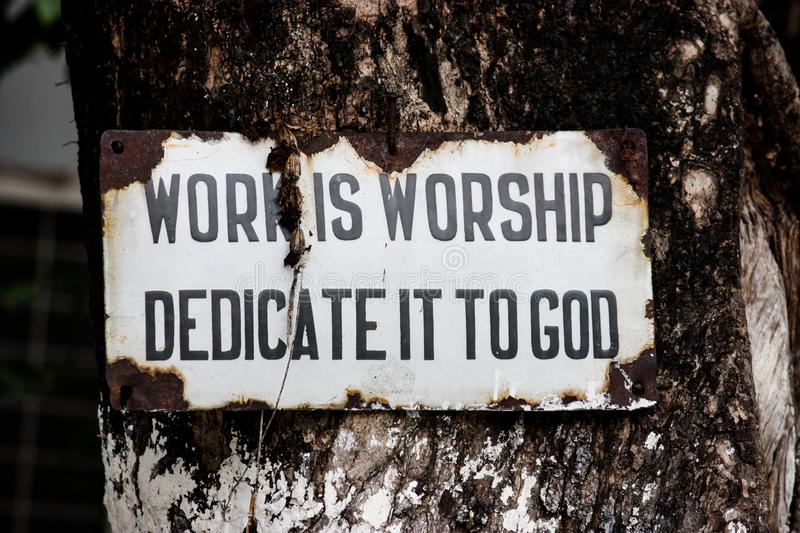 Sign with the words `work is worship dedicate it to god` ruined and hanging from a tree in Rishikesh. Uttarakhand, India royalty free stock photo