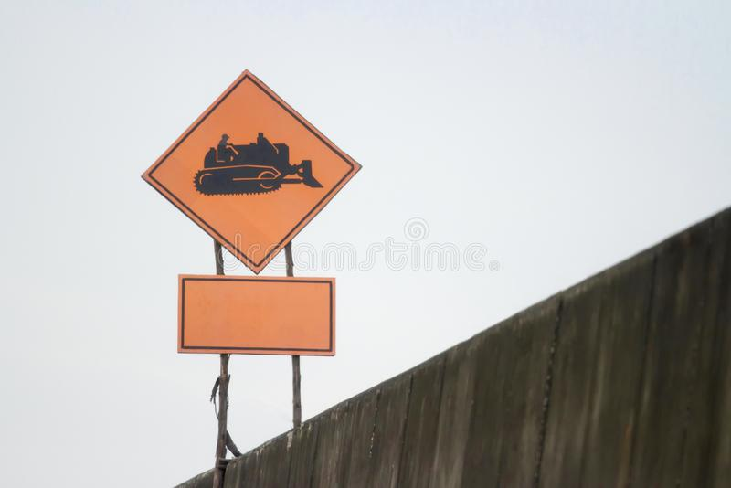 Sign for working tractor black symbol orange background.  stock photo