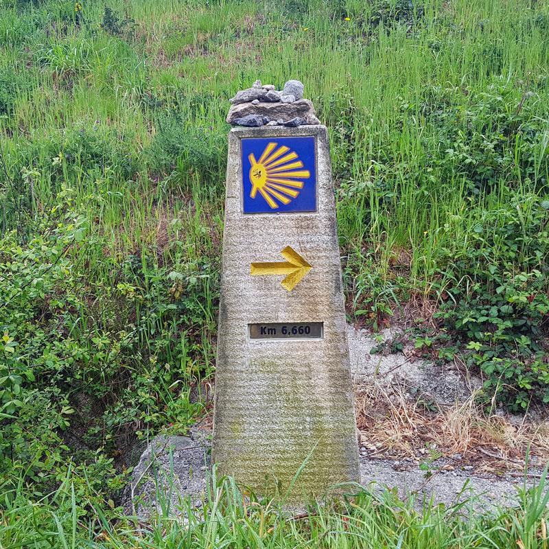 Landscape with yellow scallop shell signing the way to santiago de compostela on the Saint James pilgrimage route, Camino stock photography