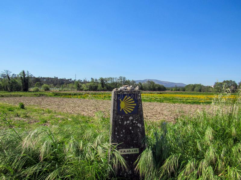 Landscape with yellow scallop shell signing the way to santiago de compostela on the Saint James pilgrimage route, Camino. Sign with yellow scallop shell signing royalty free stock image