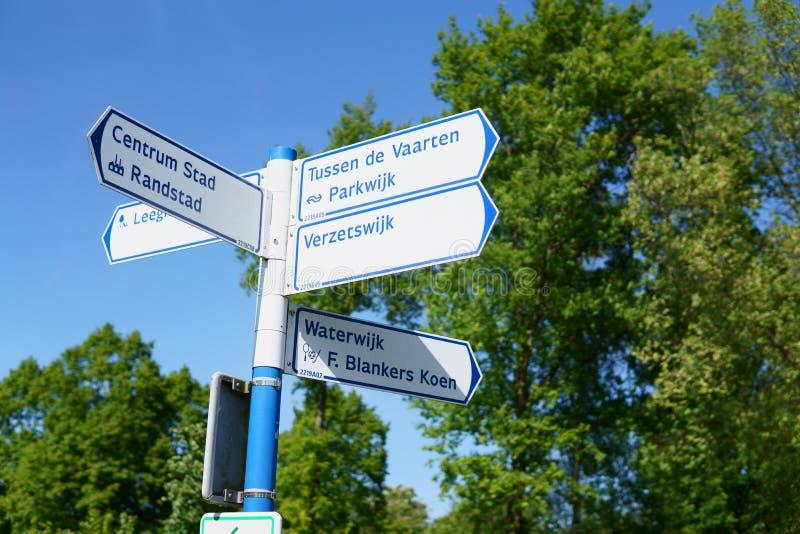 Signage in a forest in Almere, The Netherlands. Signage in Almere, The Netherlands. Signage to `Tussen de Vaarten`, `Parkwijk`, `Verzetswijk`, `Almere stad` and stock photo