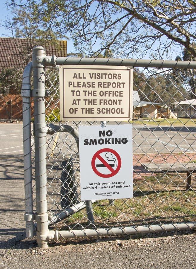 Signage non-fumeurs et autre à l'entrée d'une école image libre de droits