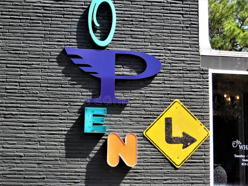 Signage on small business. Open sign on small business spelled with letters of different styles, sizes and colors, with yellow traffic sign pointing to entrance stock image