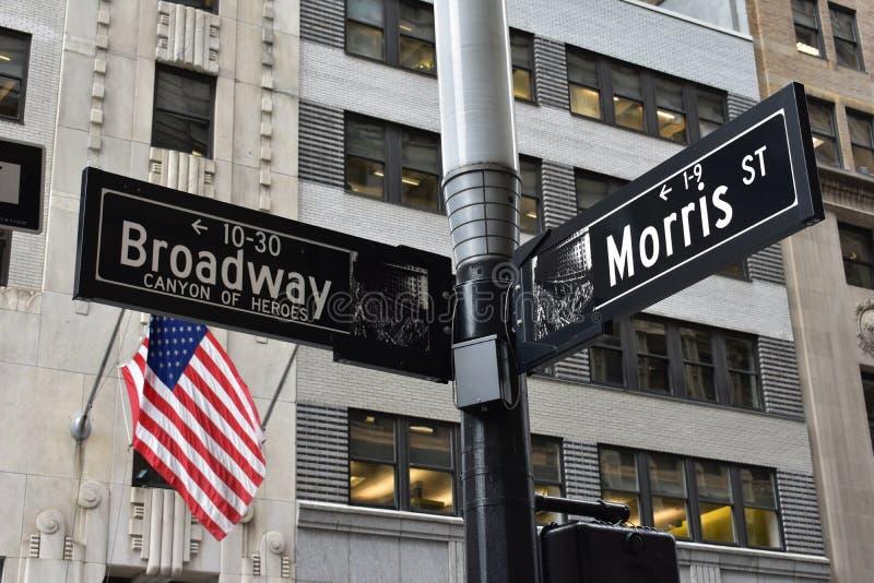 Серый цвет и черный Signage улицы Бродвей и Моррис около u S Флаг стоковые фотографии rf