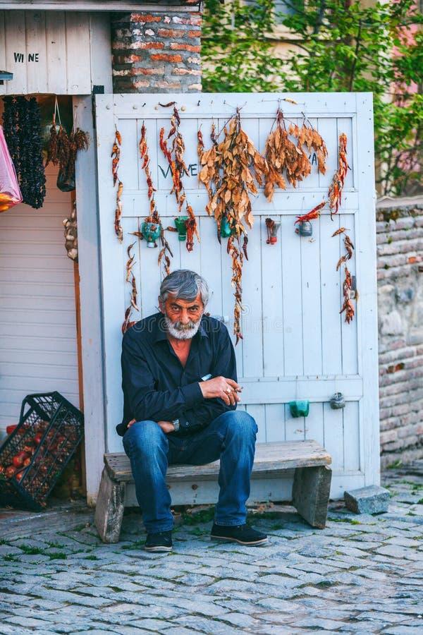 Charismatic Georgian man sits in Sighnaghi town fortress, Kakheti region, Georgia. Signagi, Georgia - 20 April, 2017: Charismatic Georgian man sits Sighnaghi royalty free stock photos