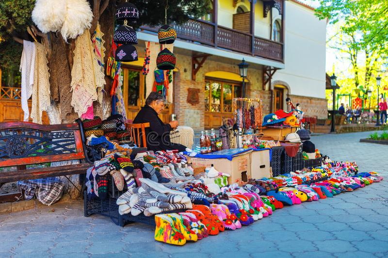 Woman female vendor sells and knits woolen slippers and socks in Sighnaghi town, Kakheti region, Georgia. Signagi, Georgia - 20 April, 2017: Woman female vendor stock image