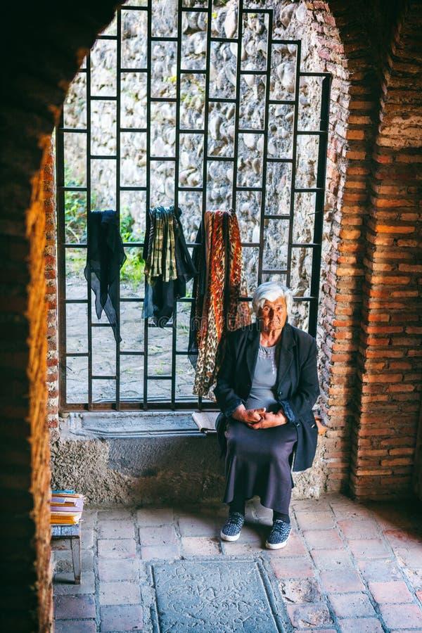 Woman female vendor sells souvenirin Sighnaghi town fortress, Kakheti region, Georgia. Signagi, Georgia - 20 April, 2017: Woman female vendor sells souvenirin stock image