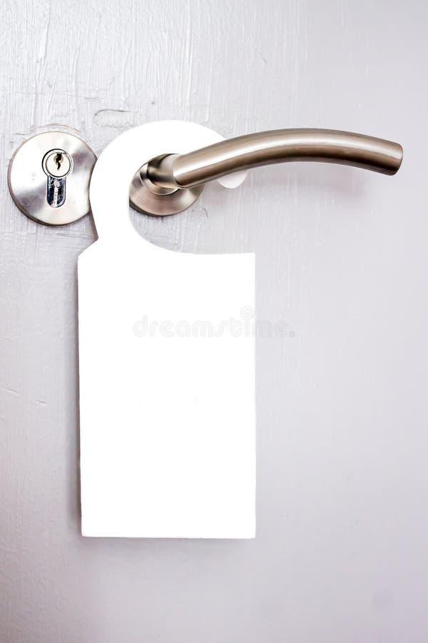 Signal blanc accrochant sur une poignée de porte des hôtels image libre de droits